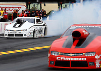 Oct 3, 2014; Mohnton, PA, USA; NHRA pro stock driver Shane Gray (left) does a burnout alongside Erica Enders-Stevens during qualifying for the NHRA Nationals at Maple Grove Raceway. Mandatory Credit: Mark J. Rebilas-USA TODAY Sports
