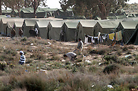 Men pray in a field by tents set up by the Tunisian army near the border. Thousands of people, mainly Egyptian workers, fled unrest in Libya and cross the border into Tunisia. Some slept in the open for several days before being processed. .At the same time forces loyal to Col. Gaddafi fought opposition forces in various parts of the country.