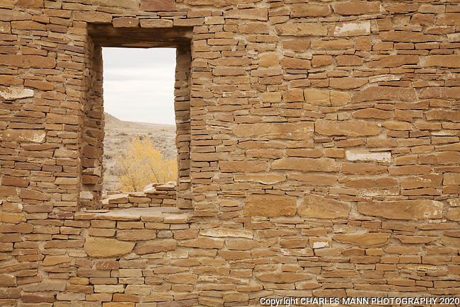 Cottonwood trees and a bit of sky are visible through a window at the Pueblo del Arroyo ruins in Chaco Culutre National Historical Park.