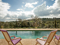 Wooden rocking chairs with purple fabric seats are the perfect place to sit by the pool and enjoy the spectacular view of the lush hills