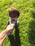 One year old child running on the grass holding his father's hand, artistic dynamc photo with motion blur.