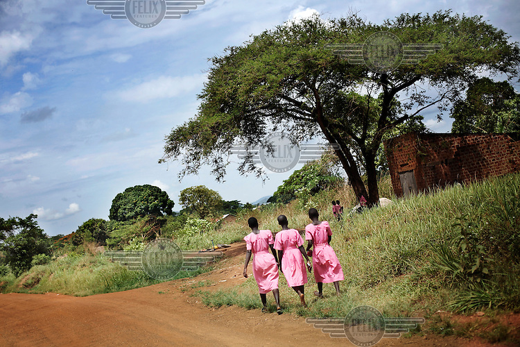 Three girls walk along a road in Northern Uganda.