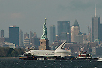 The space shuttle Enterprise is towed by barge past Statue of Liberty June 3, 2012 in New York on its way to dock in Port Elizabeth, New Jersey. Enterprise is scheduled to be moved by barge June 5 to the Intrepid Sea.  Photo by Kena Betancur / VIEWpress..