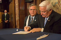 Fmr. Florida Gov. Jeb Bush, left,  of the National Constitution Center and Pennsylvania Gov. Tom Corbett symbolically sign an agreement with quill pens at the New York Public Library announcement of the agreement to display the library's copy of the original Bill of Rights at the unveiling of the document at the main branch of the library in New York on Wednesday, May 22, 2013. The over 200 year old document is one of 14 copies made and distributed to the 13 former colonies and the federal government. This copy has not been displayed for decades and a state of the art box containing protective glass and argon gas to prevent deterioration is being constructed for it. The copy will be displayed by the National Constitution Center in Philadelphia from 2014 to 2017 and then traveling back to the NYPL where the library will continue to display it 60 percent of the time. (© Richard B. levine)