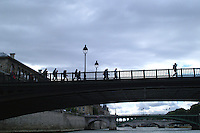 Silhouetted pedestrians cross the bridges of Paris.