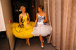 WOMEN DRESSED UP FOR BALLROOM DANCING COMPETITION, CHATTING TOGETHER AS THEY WALK ALONG CORRIDOR BEHIND THE SCENES,
