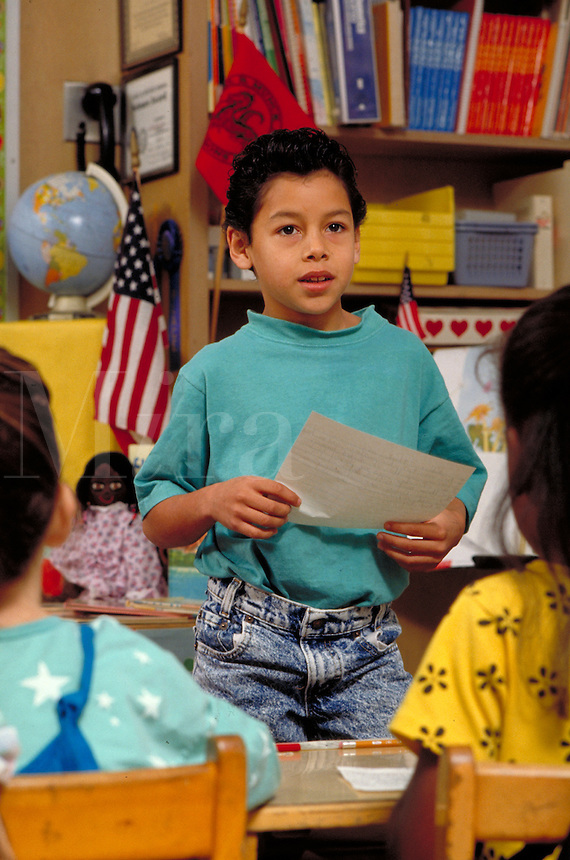 HISPANIC BOY (8) STANDING AT THE FRONT OF CLASS AND READING HIS ESSAY. HISPANIC BOY (8). OAKLAND CALIFORNIA.