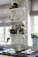 Grey linen blinds and white-painted woodwork create a cool and calm atmosphere in the kitchen