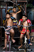 Som Mai Noi (left down) 10 years old, and the brothers One Pi Chit (center) 7 years old and One Pi Chie (right down) 9 years old are posing in one day training after school at one of the various street gyms in Bangkok. Over though is banned by law, in the streets of Thailand thousands of kids are training daily to attain a dream, become a Muay Thai champions one day, getting wealth and fame to leave out poverty and lackness instead. One by thousand each shall get it, meanwhile mostly of them will go keeping on the way to be someone.