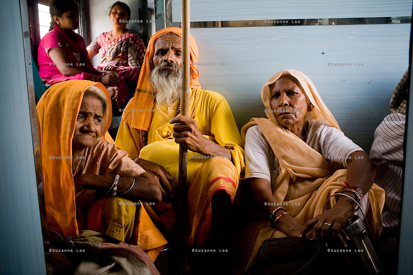 Village folk passengers ride near the door of the Himsagar Express 6318 while passing through Haryana on 7th July 2009.. .6318 / Himsagar Express, India's longest single train journey, spanning 3720 kms, going from the mountains (Hima) to the seas (Sagar), from Jammu and Kashmir state of the Indian Himalayas to Kanyakumari, which is the southern most tip of India...Photo by Suzanne Lee / for The National