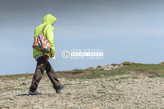 A walker on East Pentire Headland in Newquay, Cornwall.