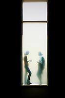 due persone in trasparenza dietro una vetrata