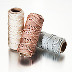 Three rolls of decorator colored string sit one atop the other in a pile on a semi-reflective surface