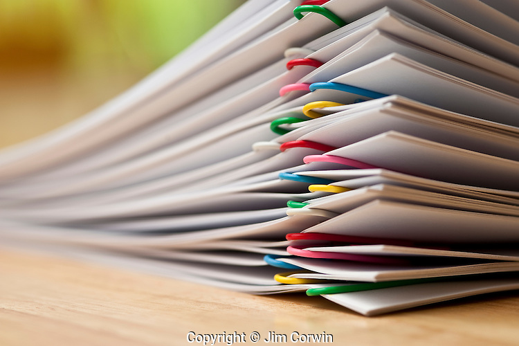 Documents stacked with multicolored paper clips close-ups