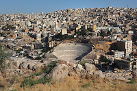 Roman Theatre, downtown Amman, Jordan. Built during the reign of Antonius Pius (138-161AD), the large and steeply raked theatre could seat 6000 people and is divided into 3 tiers. It is built into the hillside, and oriented north to keep the sun off the spectators and was restored in 1957. View from above with cityscape of downtown Amman in the background. Picture by Manuel Cohen