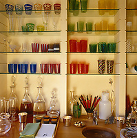 The glass shelves of the cherrywood bar house a collection of multi-coloured Venetian glasses