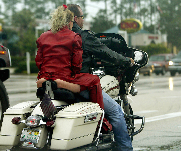 Woman in a thong and leather chaps rides down the road on a harley