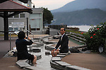 A couple taking pictures of themselves with Sakurajima behind while they put their feet on Ashi Yu. Kyushu. Japan.