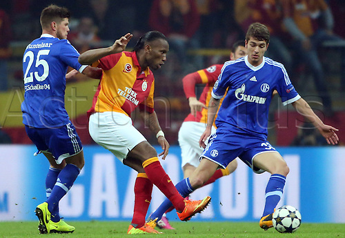 20.02.2013. Istanbul, Turkey.  Galatasaray's Didier Drogba (C) challenges with Klaas-Jan Huntelaar (L) and Roman Neustaedter (R) of Schalke during the UEFA Champions League round of 16 first leg soccer match between Galatasaray Istanbul and FC Schalke 04 at Ali Sami Yen Spor Kompleksi stadium in Istanbul, Turkey.