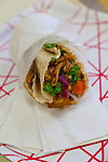 "College Falafel, widely considered one of the best shawarma shops in the city of Toronto, is located on Ossington Ave.  Shawarma is an Arab sandwich-like wrap of shaved lamb, goat, chicken, turkey, beef, or a mixture thereof. The meat is placed on a spit, and may be grilled for as long as a day. Shawarma is a fast-food staple across the Middle East, Europe and the Caucasus. Shawarma is eaten with pita bread, lavash, tabbouleh, fattoush, taboon bread, tomato and cucumber. Toppings include tahini, hummus, pickled turnips and amba. The word shawarma comes from the Turkish word çevirme, 'turning', though the dish is usually called döner kebab 'turning kebab' in Turkish. In Armenian, it is ""tarna"", literally meaning ""to turn."""