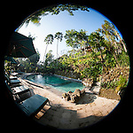 Ubud, Bali, Indonesia; a circular fisheye view of a swimming pool in early morning sunlight on the grounds of the Tjampuhan Hotel