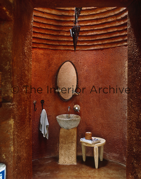 The bathroom walls are of adobe and made with the local red earth whilethe stone basin and plinth enhance the African feel of the space