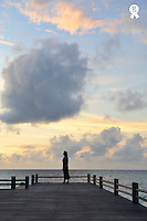 Woman contemplating sunrise on pontoon (Licence this image exclusively with Getty: http://www.gettyimages.com/detail/87990856 )