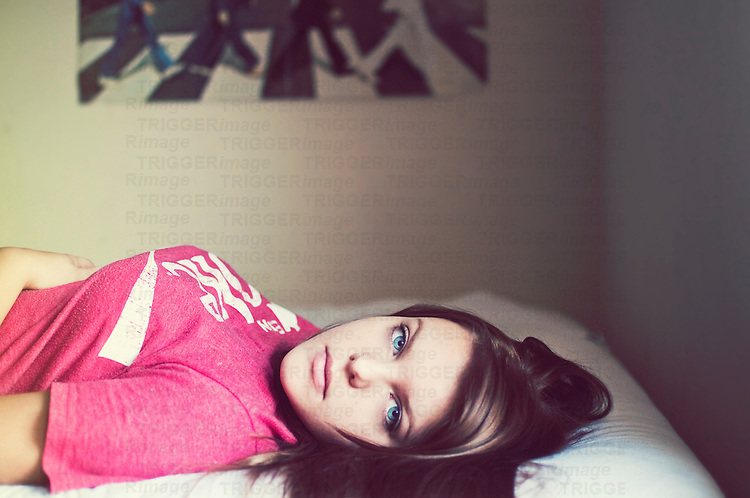 Close up of young woman with brunette hair wearing a pink shirt lying on a bed with Abbey Road Beatles poster on wall