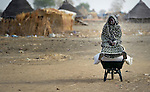 A displaced woman pauses to rest as she carries home grain in a wheel barrow in Agok, a town in the contested Abyei region where tens of thousands of people fled in 2011 after an attack by soldiers and militias from the northern Republic of Sudan on most parts of Abyei. Although the 2005 Comprehensive Peace Agreement called for residents of Abyei--which sits on the border between Sudan and South Sudan--to hold a referendum on whether they wanted to align with the north or the newly independent South Sudan, the government in Khartoum and northern-backed Misseriya nomads, excluded from voting as they only live part of the year in Abyei, blocked the vote and attacked the majority Dinka Ngok population. The African Union has proposed a new peace plan, including a referendum to be held in October 2013, but it has been rejected by the Misseriya and Khartoum. The Catholic parish of Abyei, with support from Caritas South Sudan and other international church partners, has maintained its pastoral presence among the displaced and assisted them with food, shelter, and other relief supplies.
