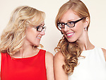 Portrait of two smiling sisters with blond hair looking at each other wearing glasses
