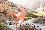 Woman outdoors in the yoga pose natarajasana or dancer's pose in the mountains.