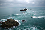 A fishing boat sails through an opening in the rocks at Cap du Raz, Brittany, France..