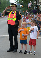 A Westerville, Ohio, police officer stands at attention and salutes with two of his small charges as the American flag passes in review at the beginning of the July 4, 2006, parade through the heart of the city.<br />