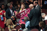 July 18, 2016 - Cleveland, Ohio: A protester from the group Code Pink struggles to unfurl her banner at the Republican National Conventions. She was one of two protesters from Code Pink who attempted to disrupt the convention.