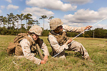 October 22, 2014. Camp LeJeune, North Carolina.<br />  Cpl. Angelique Preston, age 21, left, of artillery Battery A of the Ground Combat Element Integrated Task Force, ties down a tent cord as her unit rushes to camouflage their trucks and howitzers.<br />  The Ground Combat Element Integrated Task Force is a battalion level unit created in an effort to assess Marines in a series of physical and medical tests to establish baseline standards as the Corps analyze the best way to possibly integrate female Marines into combat arms occupational specialities, such as infantry personnel, for which they were previously not eligible. The unit will be comprised of approx. 650 Marines in total, with about 400 of those being volunteers, both male and female. <br />  Jeremy M. Lange for the Wall Street Journal<br /> COED