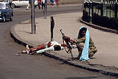 Addis Ababa, Ethiopia<br /> May 30, 1991<br /> <br /> A demonstrator opposing the new government was shot and left in the street for public display. He is guarded by a member for the new military rebels.<br /> <br /> In late May 1991 the long civil war in Ethiopia came to a climax when the alliance of four rebel groups, the Ethiopian People's Revolutionary Democratic Front (EPRDF), toppled the authoritarian government of Mengistu Haile-Mariam and took control of Addis Ababa and the nation. The governing regime declared a cease-fire and fled. <br /> <br /> In July 1991 the 24 different groups met in the capital and established a multi-party provisional government headed by Meles Zenawi, the Tigray Rebel Leader, to lead the country to its first free elections within two years.