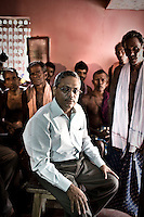 "Anti-Posco leader and president of Posco Pratirodha Sangram Samiti, Mr. Abhaya Sahoo, with local villagers in Nuagaon village. Sahoo has been spearheading the anti-Posco movement in Dhinkia panchyat for three years. In October 2008 he was arrested, and spent 10 months in jail, until he was finally released on conditional bail by Orissa High Court. All the residents of this village would be displaced if plans for the new steel works are allowed to proceed. South Korean steel giant Posco continues to face stiff public resistance in Orissa's Jagatsinghpur district where the company is setting up India's biggest direct foreign investment project of a 12 million tonne steel plant, at the cost of USD 12 Billion. Villagers have formed an agitating group, ""Posco Pratirdh Sangram Samiti"" to oppose the construction of the Posco development, which will displace thousands of people and make agricultural land untenable."