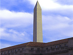 The Washington Monument rises above a nearby Washington, DC building. Undated.
