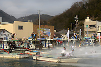"""Housui Gassen (fire-hose battle), Bizen city, Okayama pref, Japan, February 2, 2014. The annual Bizen """"Housui Gassen"""" (fire-hose battle) takes place in the Hinase port area. Opposing teams of fire-fighters spray each other with hoses before the event culminates with a display of coloured water from the hoses."""