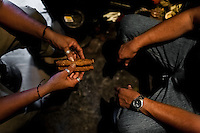 A Salvadorean 'brujo' (sorcerer) holds cigars before starting the tobacco reading ritual in a street fortune telling shop in San Salvador, El Salvador, 18 February 2014. Due to the strong historical tradition of using tobacco by indigenous shamen in Americas, nowadays, the reading of tobacco is one of the most most widespread methods of divination, employed by esoteric practitioners and healers in all Latin American countries. According to the shapes of burn leaves, colors of ash and smoke, burning velocity and other factors, the experienced fortune teller interprets the manifested signs in relation with the supposed future of people involved in the tobacco ritual.