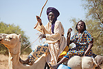 """In West Africa, certain villages have markets that """"assemble"""" at regular intervals, such as weekly or every three days.  People from villages around the region come on market day to buy and sell food, livestock, and other goods and services.  In this photo, a Tuareg man and his wife come to the village market of Bourro in northern Burkina Faso by camel."""