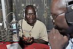 "Opi Ako Morris (left) co-hosts the morning ""Juba Sunrise"" program on the Catholic Church-sponsored Radio Bakhita in Juba, the capital of Southern Sudan. He is interviewing Omar Sebit Lado, a local historian."