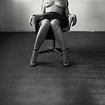 A topless woman wearing fishnet stockings sat on a chair in an empty room.