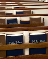 Holy Bibles and Hymnals stored in church pews.