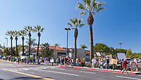 Occupy Orange County protesters march through a shopping center (past an Olive Garden) near the intersection of Alton and Culver in Irvine CA.  Sunny skies and palm trees remind us that we're in Southern California.