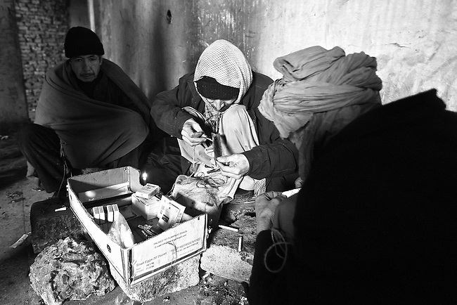 Two men smoke opium while another drifts in a narcotic haze inside the ruins of the former Soviet Cultural Center in Kabul, Afghanistan. More than 90 percent of the world's opium -- from which heroin is derived-- is produced in Afghanistan, and its cheap availability is wreaking havoc on a society already ravaged by 30 years of war. More than 2,000 addicts a day gather to use opium and heroin inside the derelict structure, which was almost completely destroyed during the 1992-1994 civil war. Feb. 2, 2009.