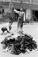 China. Province of Guangdong. The village of Beilin is part of the town of Guiyu. Men worship their dead ancestrors in a religious ceremony. The papers burnt on a fire on the road are the symbols of money sent to the ancestrors. © 2004 Didier Ruef