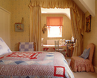 Twin beds in this children's bedroom are covered in patchwork quilts and separated by a set of curtains