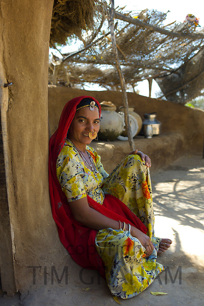 Indian Hindu woman at home made of mud bricks coated with cow dung in Bishnoi village near Rohet in Rajasthan, Northern India