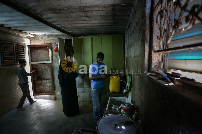 Fadi al-Shami, 21, a Palestinian blind youth (R), helps his mother in home work at their home in Central Gaza Strip on Aug 17, 2013. al-Shami lost his sight after he was injured by an Israeli airstrike next to his family home at al-Musaddar village in central Gaza Strip during the Gaza–Israel conflict in 2006. Photo by Mahmoud Hamda